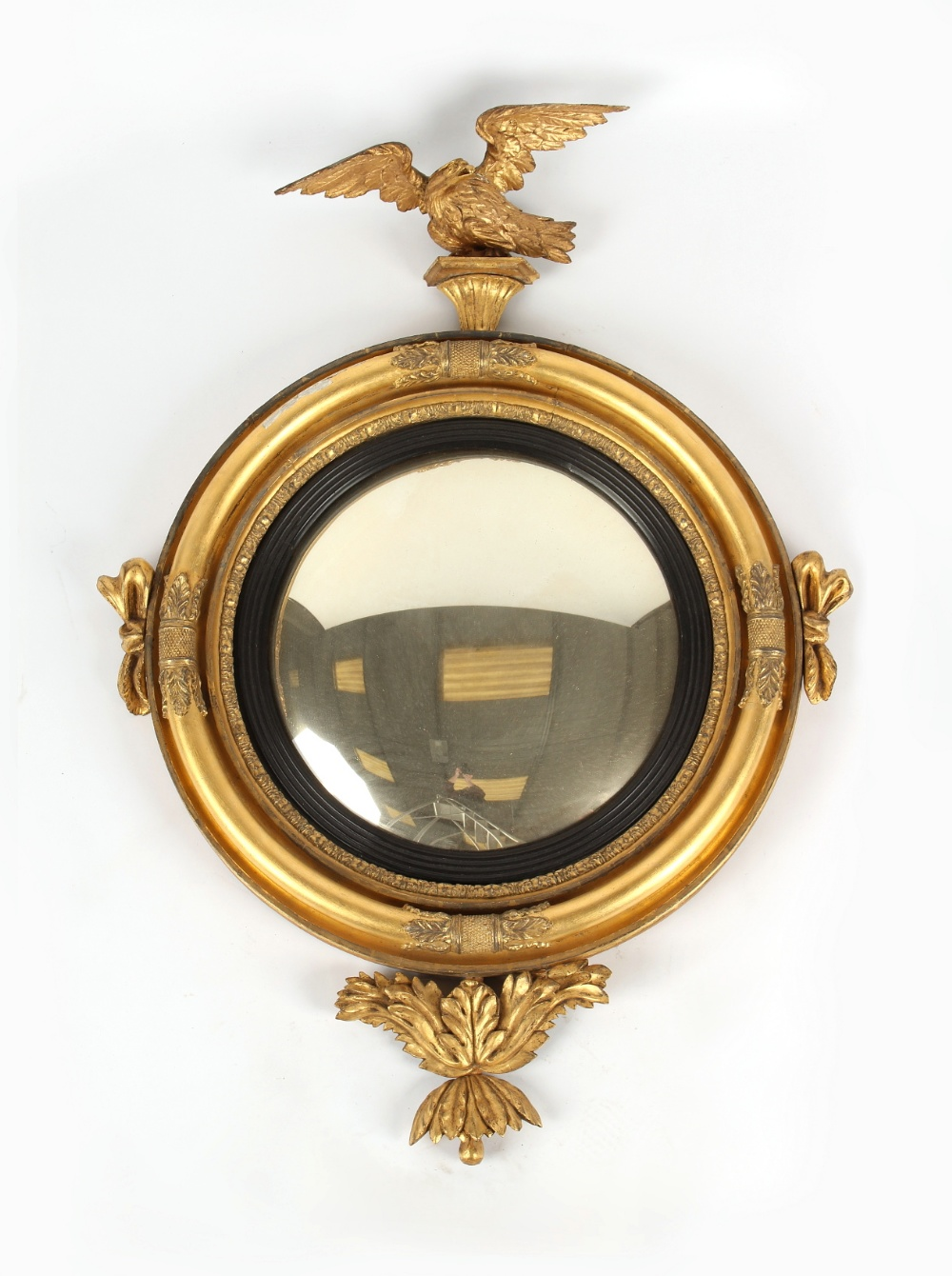 A 19th century carved giltwood framed convex mirror with eagle cresting & acanthus below, 44.