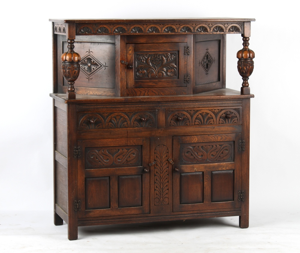 Property of a deceased estate - a reproduction carved oak court cupboard, 49ins. (124.5cms.) long.