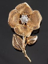 An unusual 18ct yellow gold diamond floral spray brooch, the flowerhead with hinged folding petals