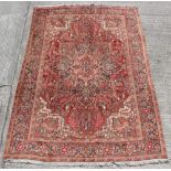 A Heriz woollen hand-made carpet with red ground, 126 by 89ins. (325 by 225cms.).