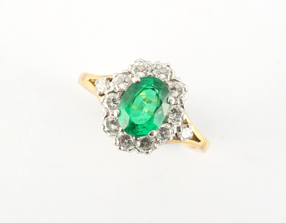An 18ct yellow gold emerald & diamond oval cluster ring, the vibrant & clear oval cushion cut