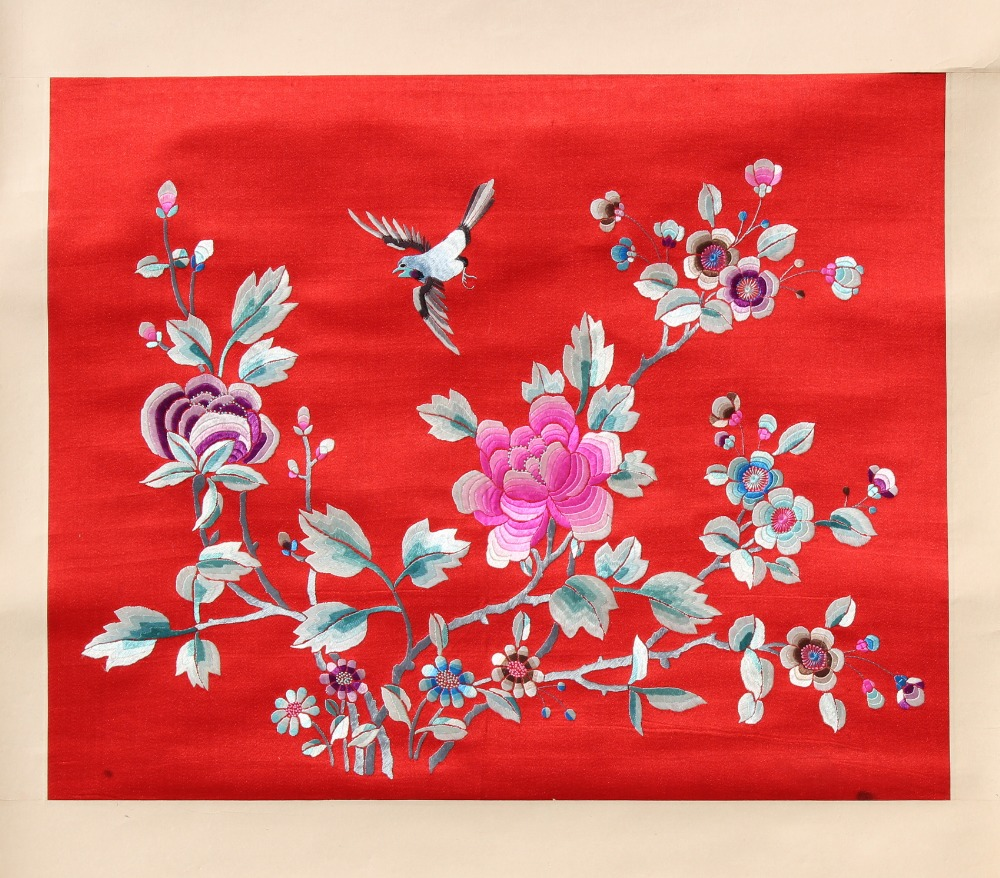 A Chinese embroidered silk scroll depicting a bird among flowers on a crimson ground, the silk 14.