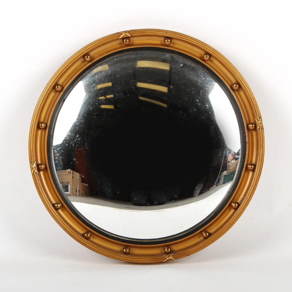 Property of a gentleman - a gilt circular framed convex mirror, first half 20th century, 21.5ins. (