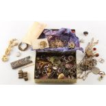A small tin containing assorted costume jewellery, etc..