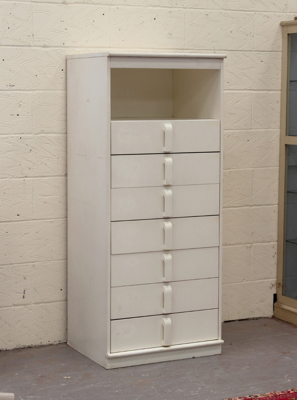 A modern white painted narrow chest of seven drawers.