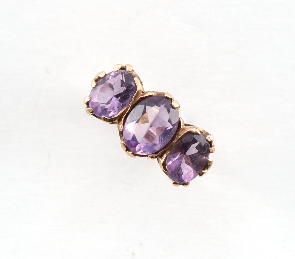 A 9ct gold ring set with three oval cut amethysts, size N, boxed.