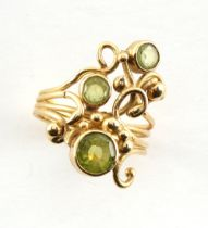 A modern 18ct yellow gold stylised scrolling foliate ring set with three round cut peridots, size Q,