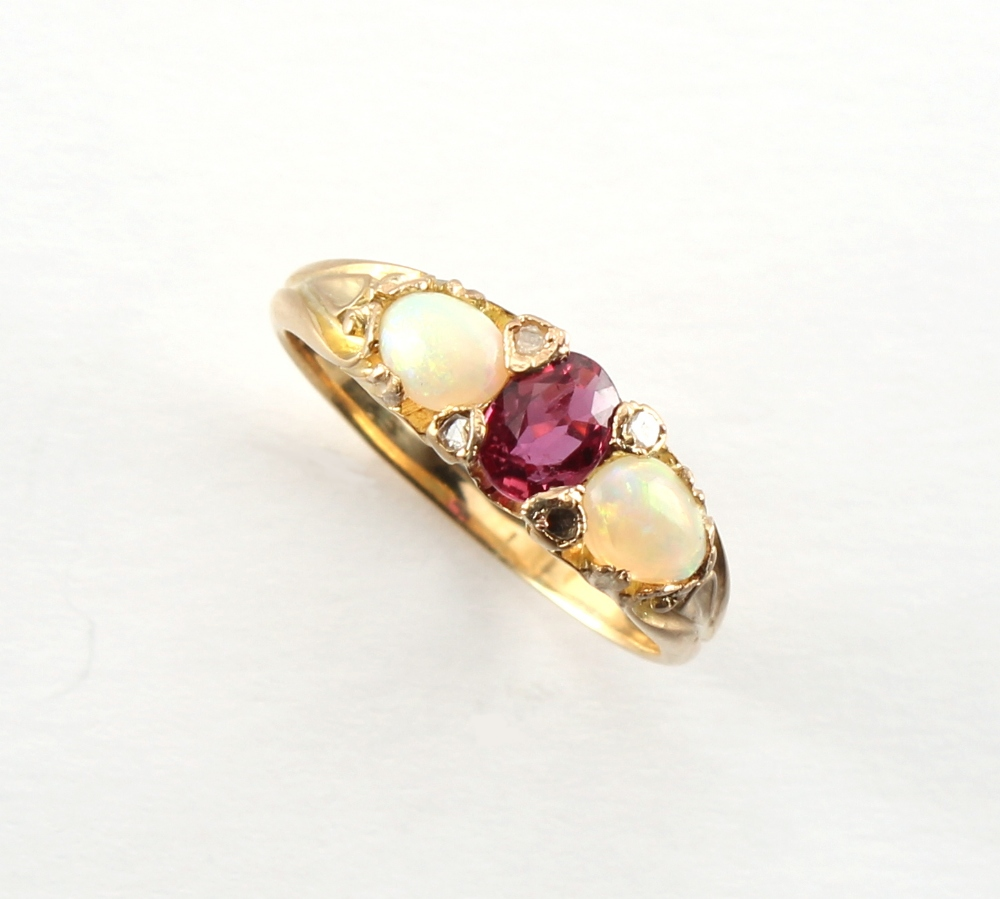 A yellow gold ruby opal & diamond ring, the central oval cushion cut ruby measuring approximately