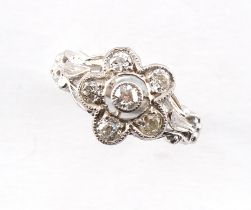 An unmarked white gold diamond flowerhead cluster ring, the six round cut diamonds in millegrain