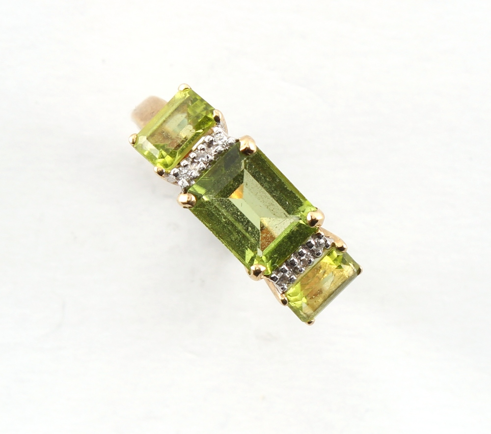 An Art Deco style 9ct yellow gold ring set with three emerald cut peridots alternating with rows