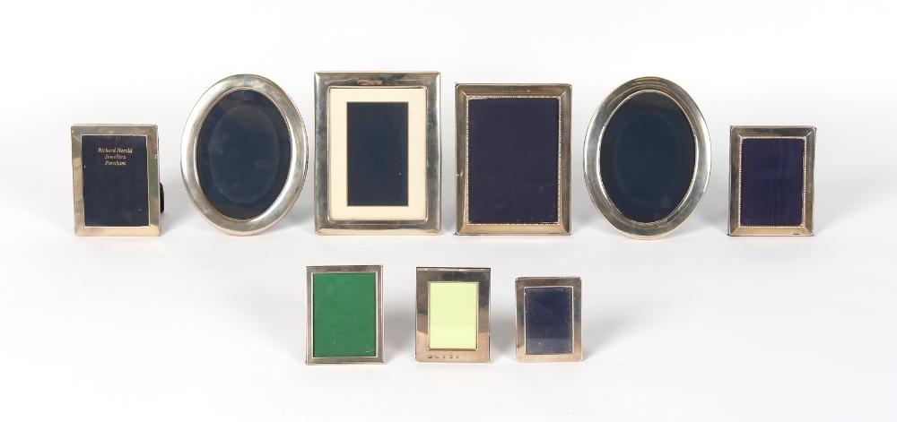 Nine modern silver easel photograph frames including a pair of oval frames, 8.75ins. (22.2cms.) high