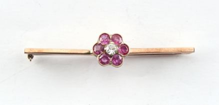 An unmarked gold ruby flowerhead bar brooch, the pin cracked, 52mm long, in associated box.