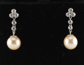 A pair of pearl & diamond earrings, with post & butterfly fastenings, each with a single untested