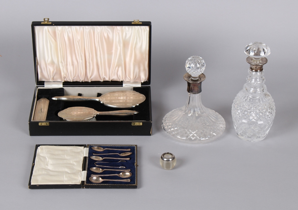 Two cut glass decanters with silver collars; together with a cased silver backed dressing table hand