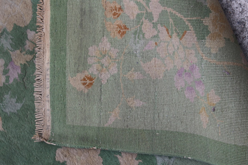 Property of a lady - a Chinese wool carpet, first half 20th century, with green ground, old moth - Image 3 of 3