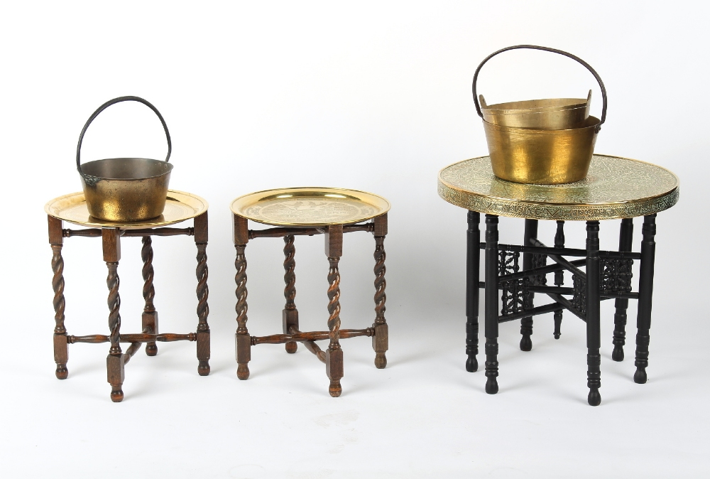 Property of a deceased estate - three brass circular topped tables on folding wooden bases; together