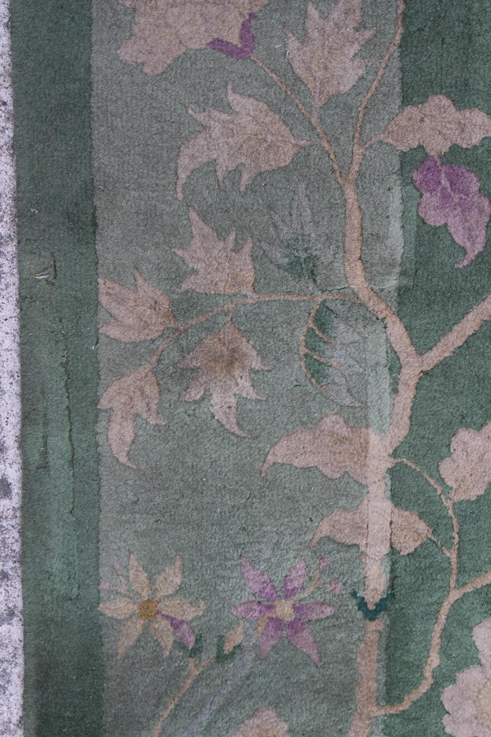 Property of a lady - a Chinese wool carpet, first half 20th century, with green ground, old moth - Image 2 of 3