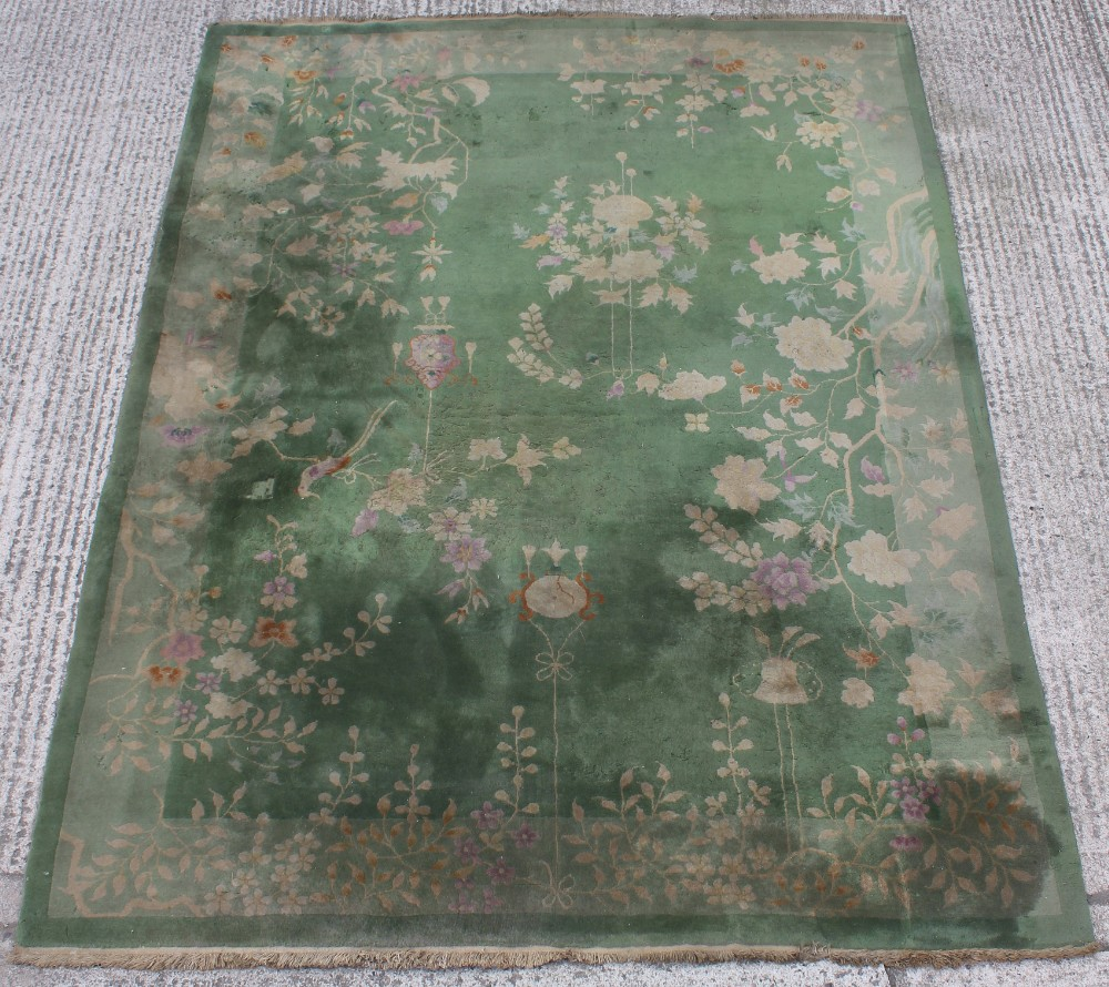 Property of a lady - a Chinese wool carpet, first half 20th century, with green ground, old moth