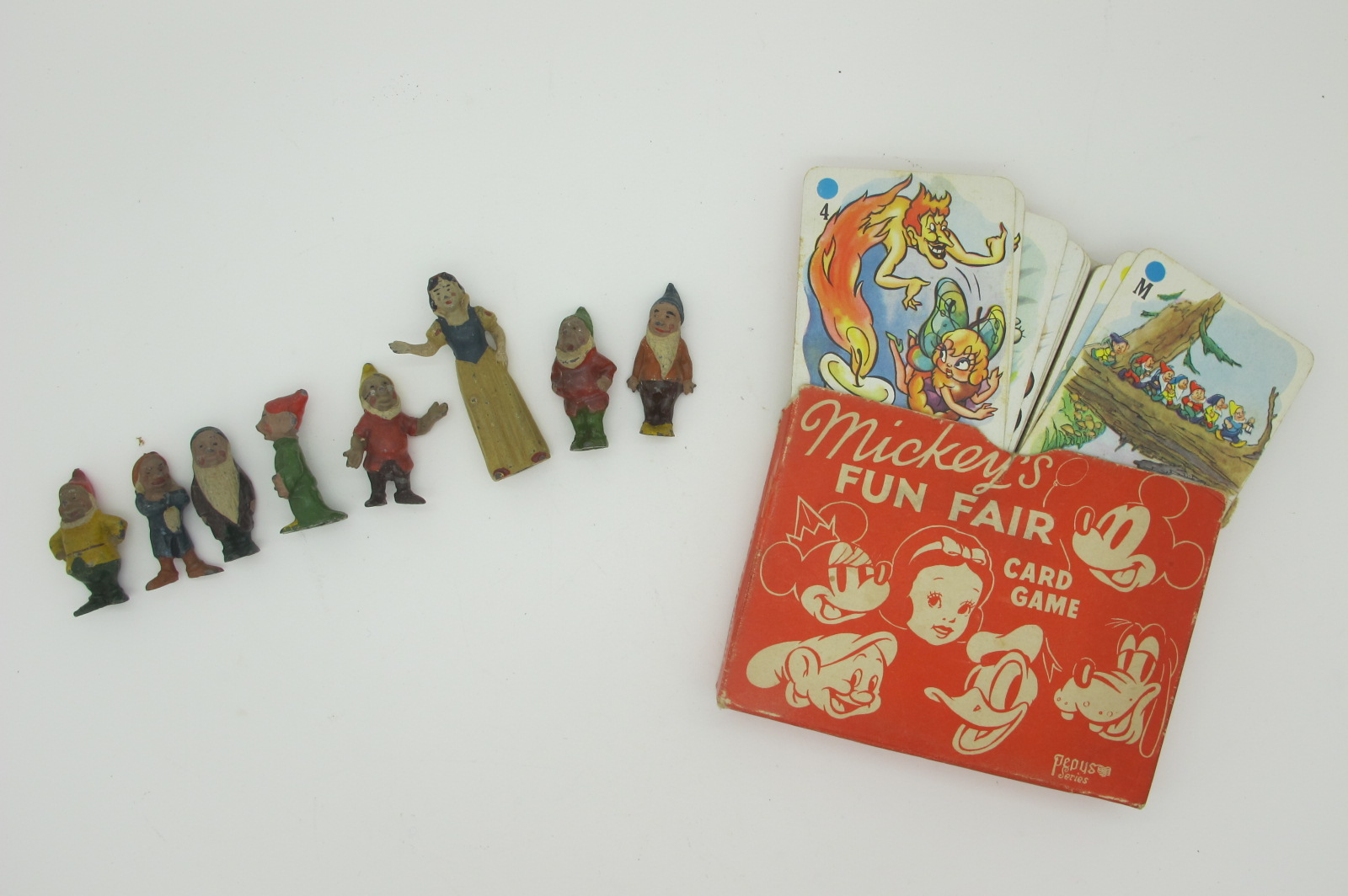 A Pre War Britains Snow White and Seven Dwarfs, appears unbroken, plus a 'Pepys' Mickeys Fun Fair