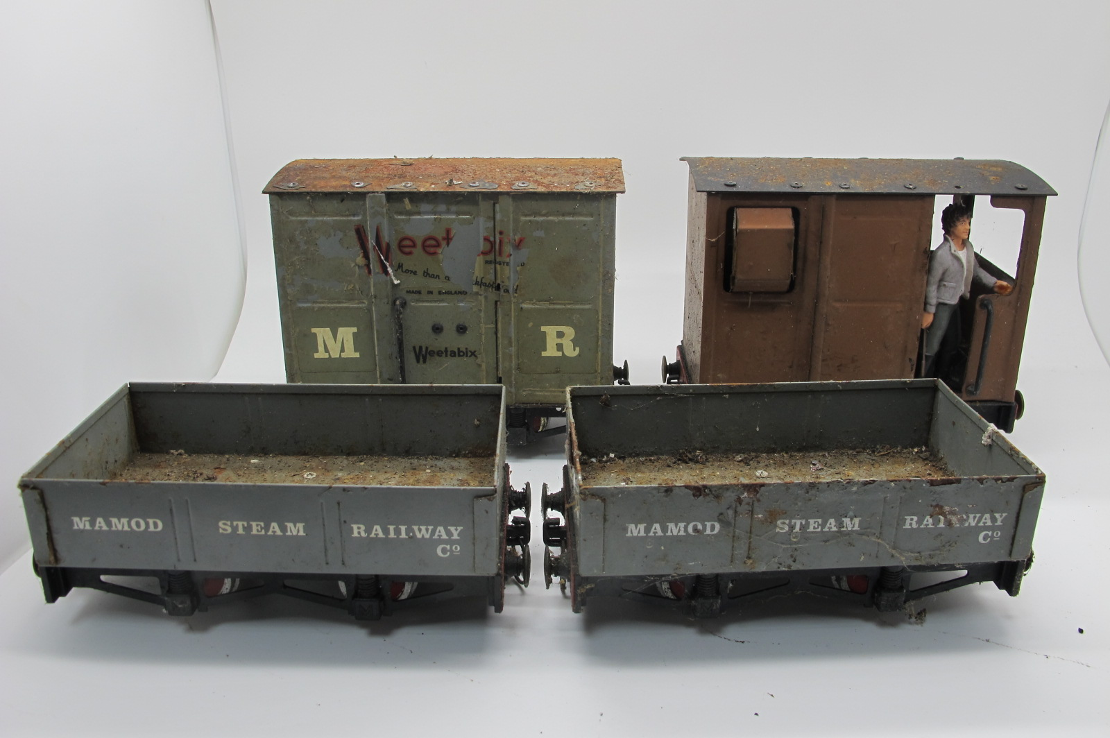 Four Mamod Live Steam Railway Rolling Stock, including two coal wagons, playworn, damaged.