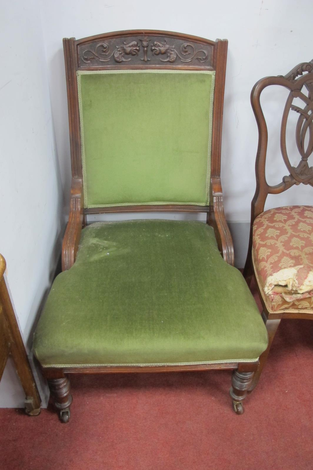 And Edwardian Salon Easy Chair, with mask carving, turned legs, upholstered in green draylon.