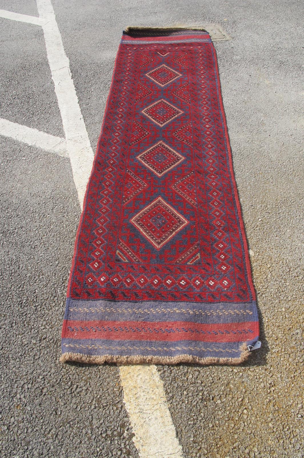 Middle Eastern Wool Runner, with four central lozenges, geometric motifs on burgundy ground, overall