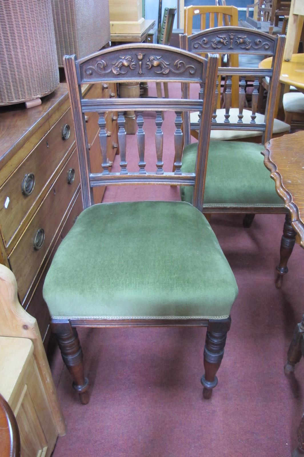 A Set of Four Early XX Century Dining Chairs, with mask carving and architectural pillar supports,