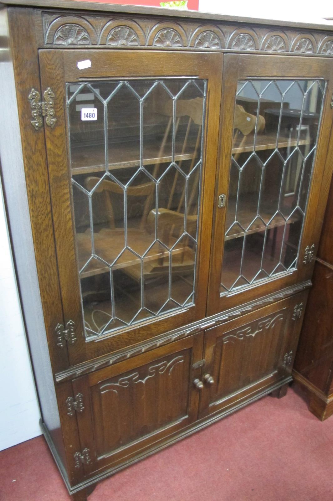 An Oak Book Cabinet, with half wheel carving, honeycomb lead glazed doors, over linen fold