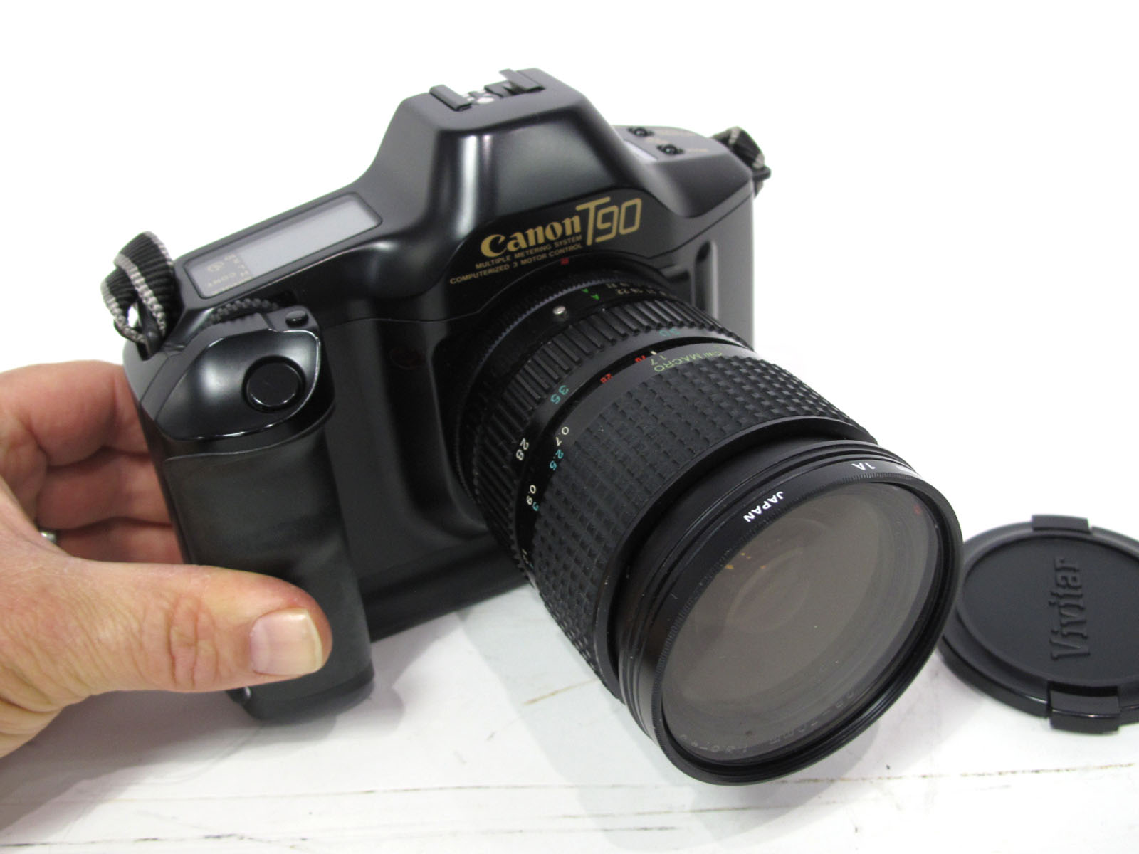 Canon Camera T90, computerised three motor control, with Tokina 28-70mm lens with carry case.