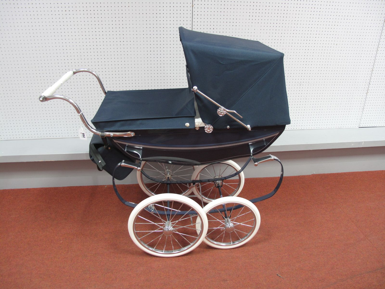 A Silver Cross Dolls Pram, with navy blue cover, hood and bag, with blue sides.