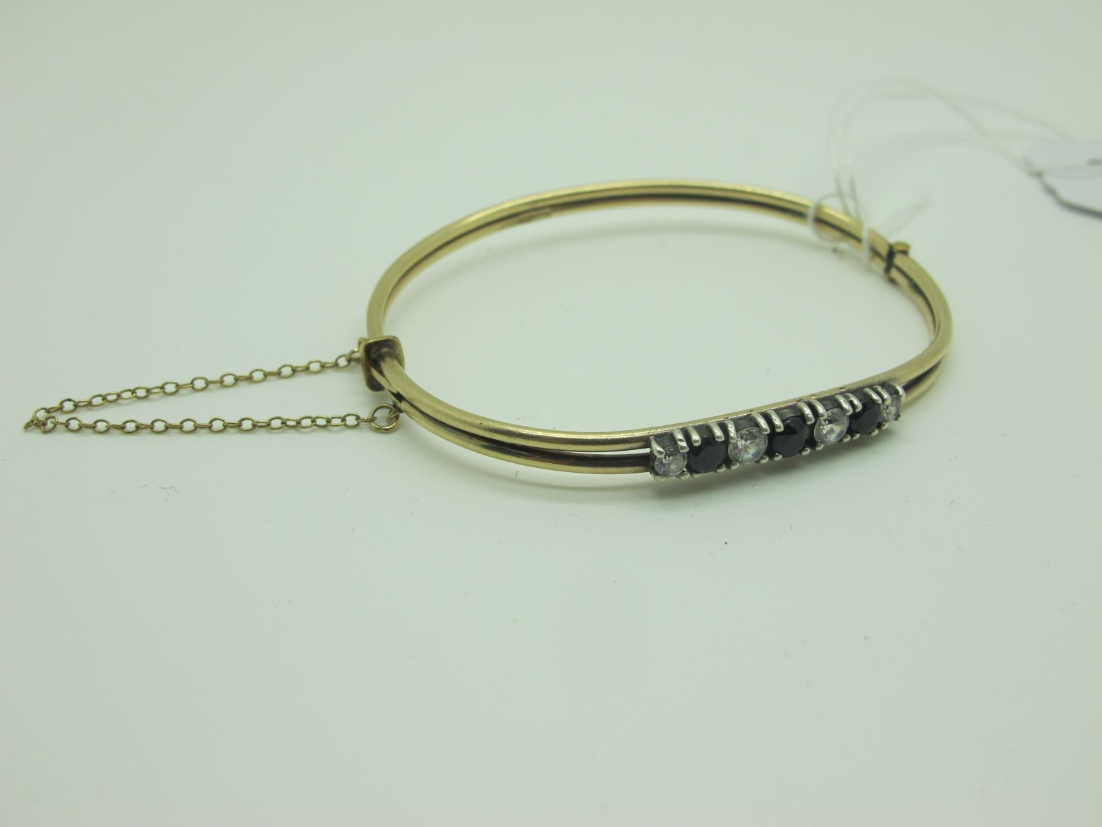 A Fancy Bangle, of two row design, alternate claw set details, to snap clasp, with safety chain,