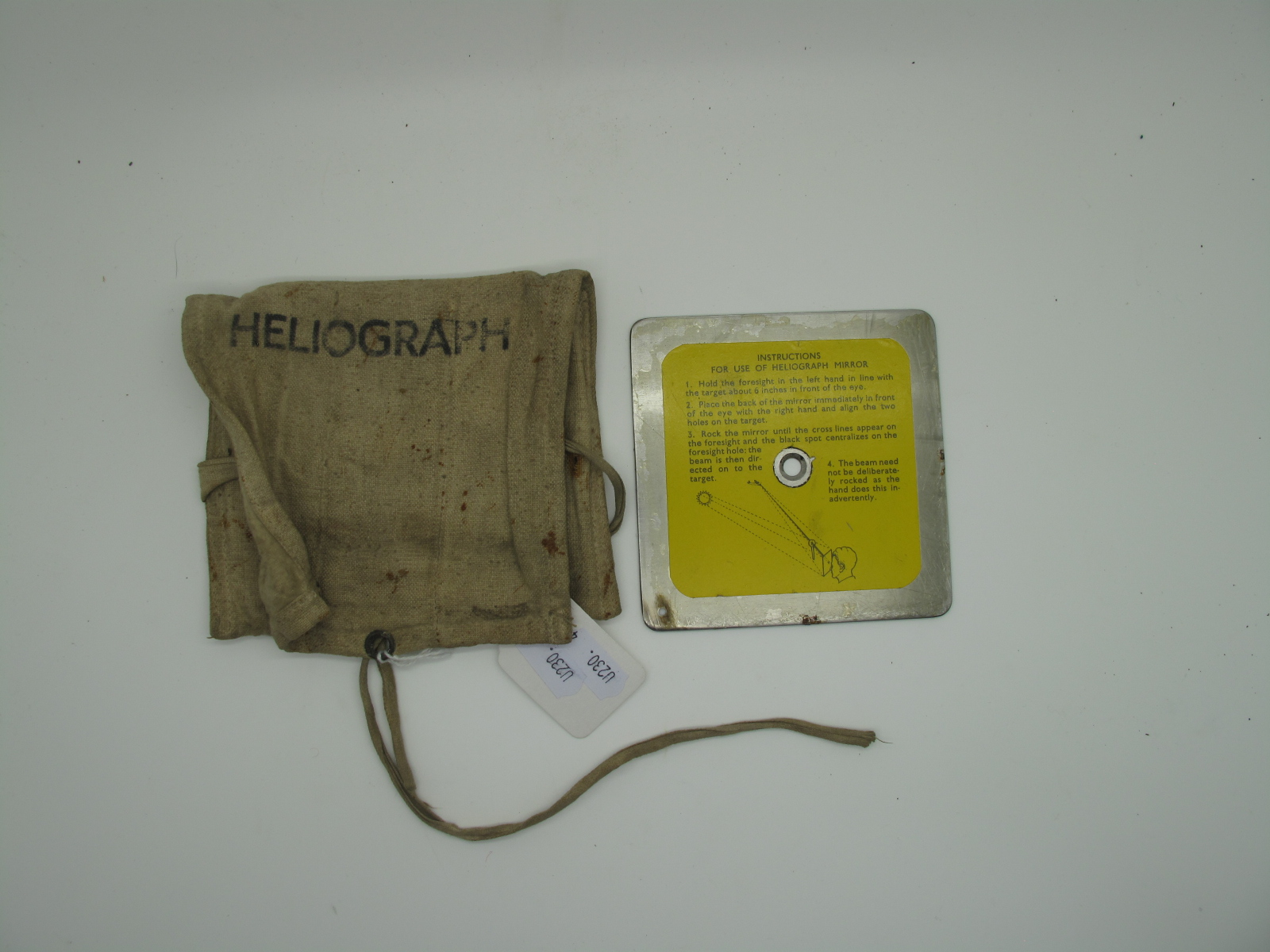 A WWII Era Heliograph Signal Mirror, in canvas 'Heliograph' bag, including instructional sticker