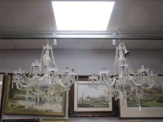 Two Chandeliers, each with nine fluted branches, the sconces hung with prismatic drops between