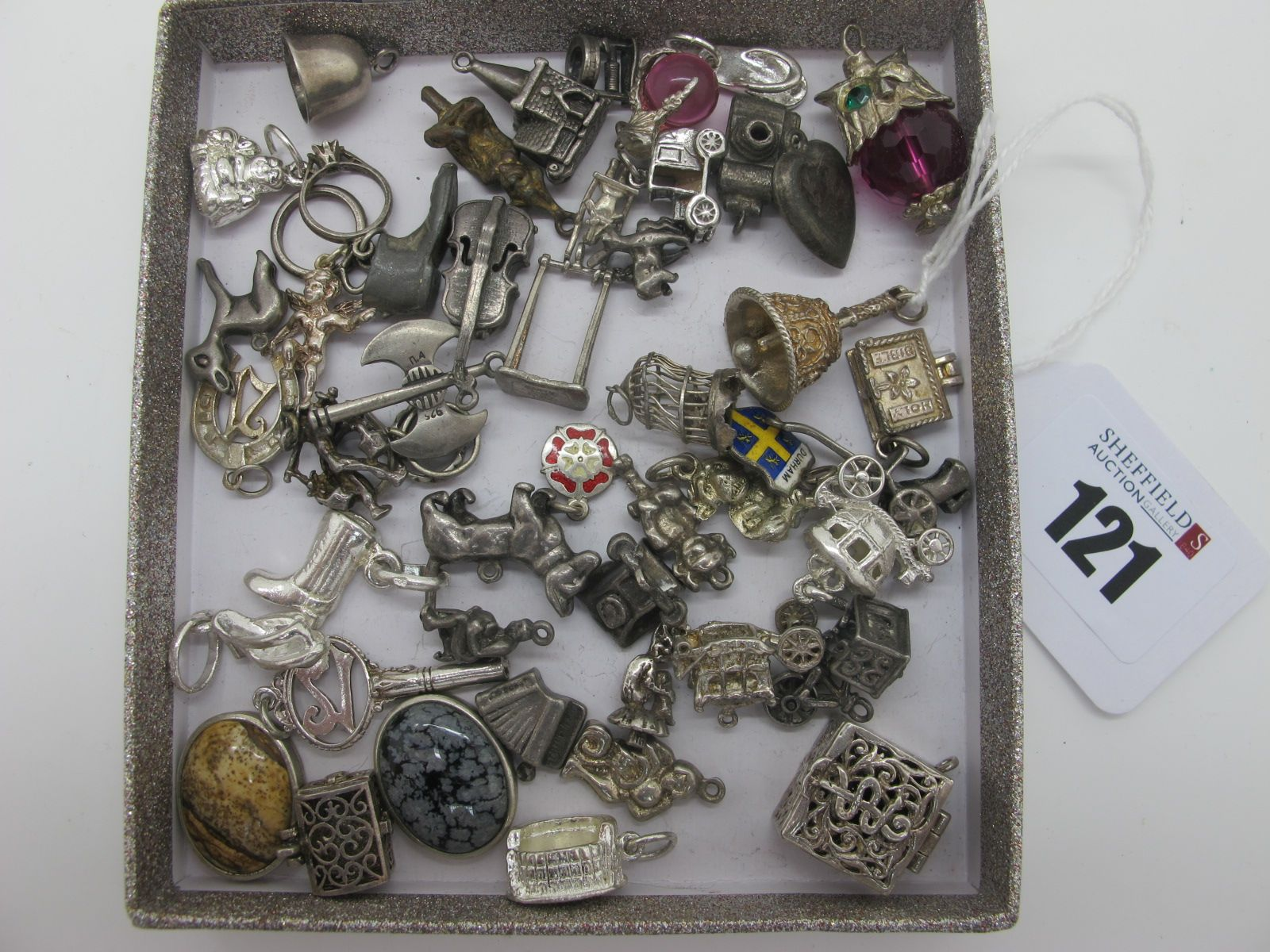 A Collection of Assorted Novelty Charm Pendants, including bell, birdcage, 21 horseshoe, cello,