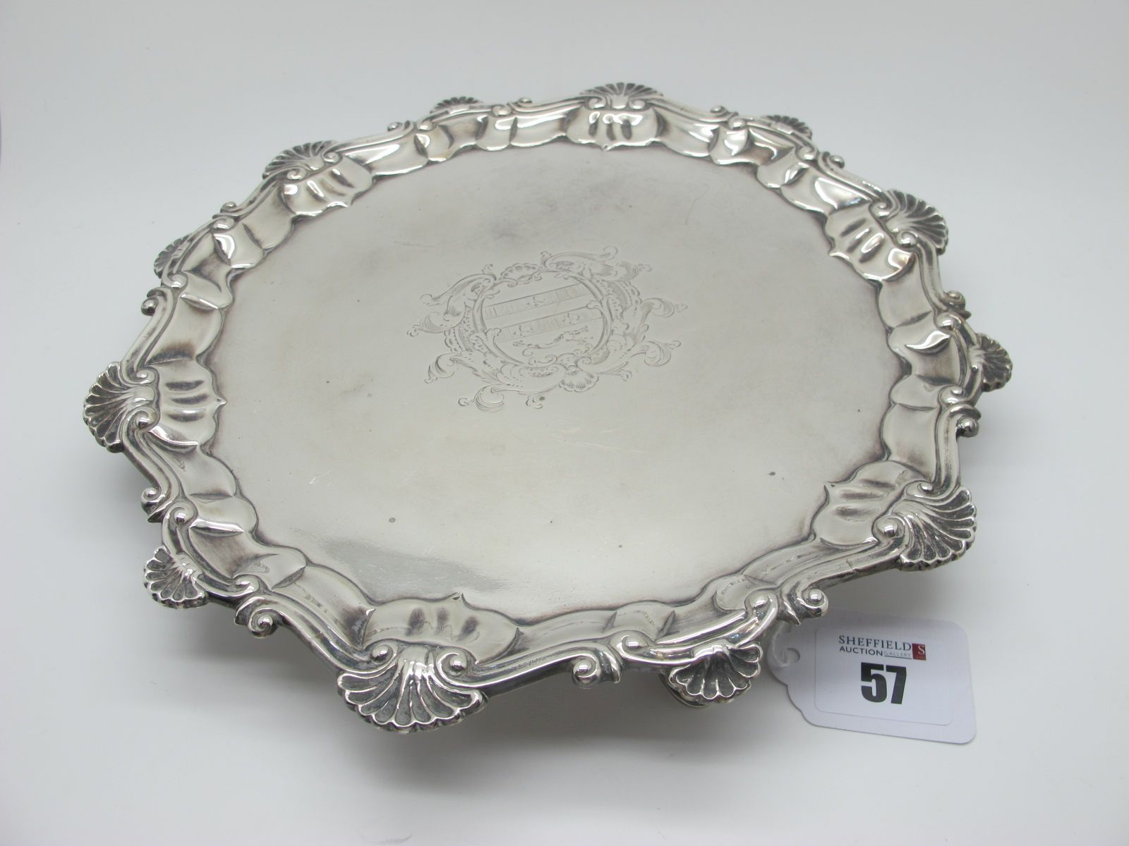 A Hallmarked Silver Salver, Ebenezer Coker, London 1755, of circular form, within shaped shell and