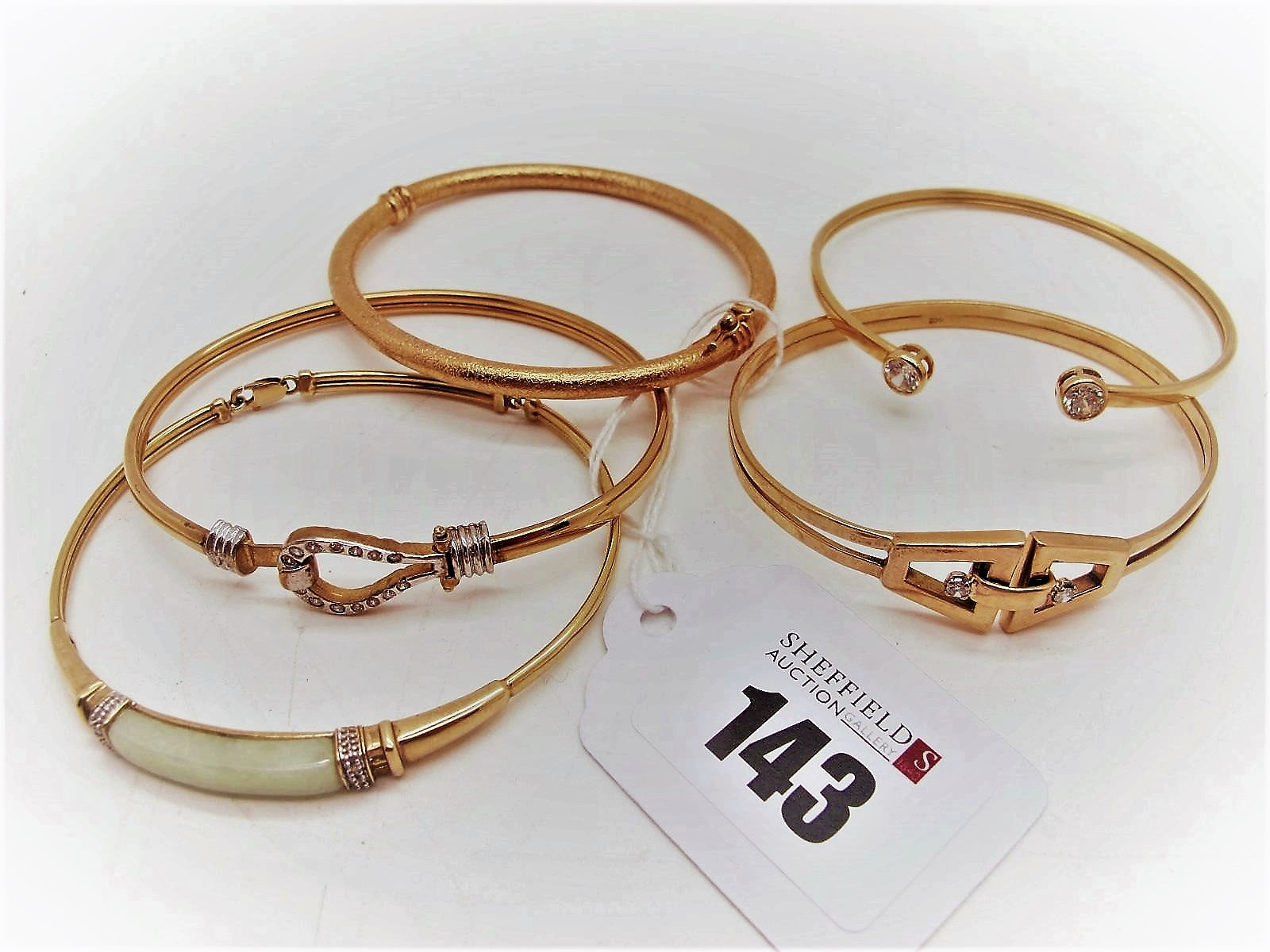 A 9ct Gold Bangle, with loop and hook fastener; together with a hinged bangle, of textured finish; a