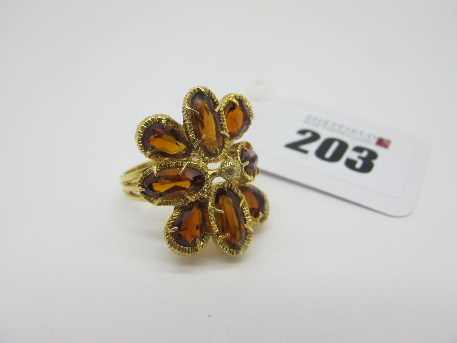 """A Modern Cluster Dress Ring, oval and teardrop claw set, stamped """"750"""" (finger size R)."""