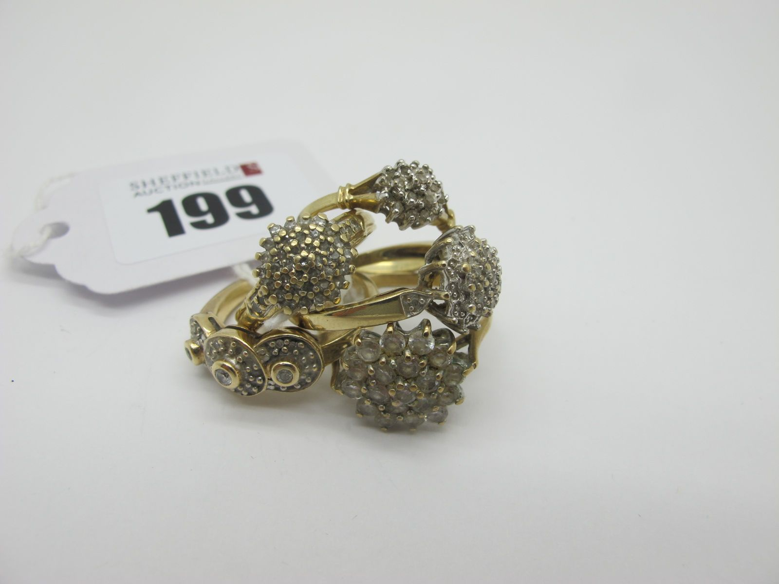 A 9ct Golf Diamond Cluster Ring, claw set (finger size P); together with four further 9ct gold dress