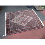 A Middle Eastern Wool Tasselled Rug, with allover geometric motifs, diamond shapes to centre, on red