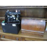A Singer Sewing Machine, in oak dome topped case, an electric example in black early case, (untested