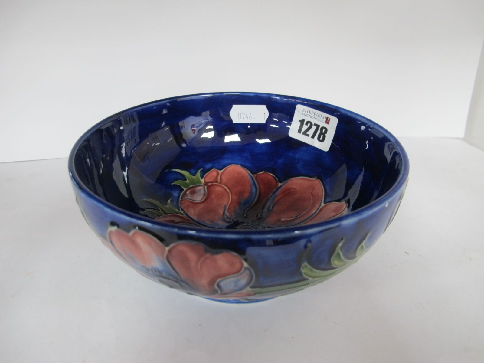 A Moorcroft Pottery Bowl, red floral decoration on blue ground, 16cm diameter, painted and impressed
