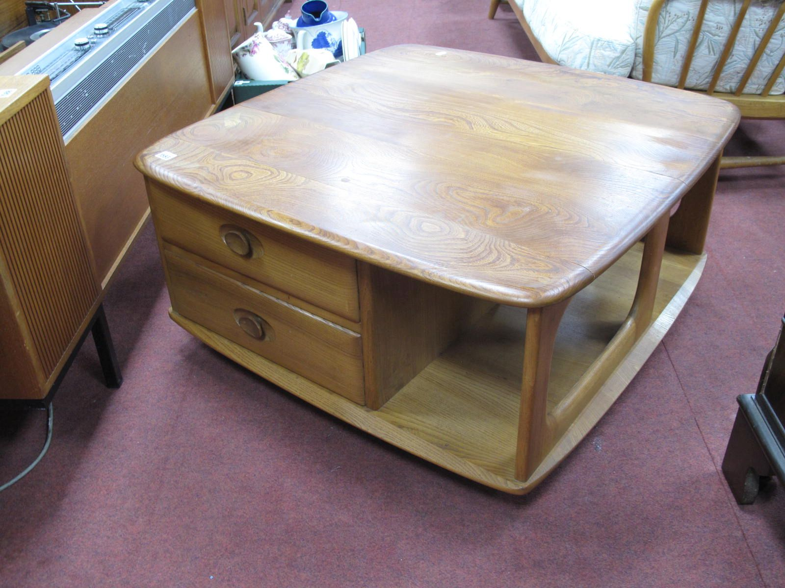 An Ercol Coffee Table, of square form, with rounded corners, two drawers and open magazine