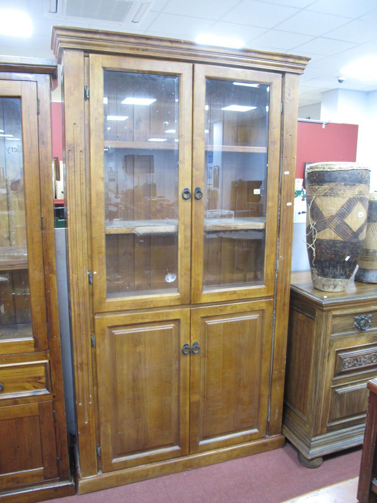 A Teak Bookcase, over a stepped cornice, glazed doors, two internal shelves, over panelled doors,