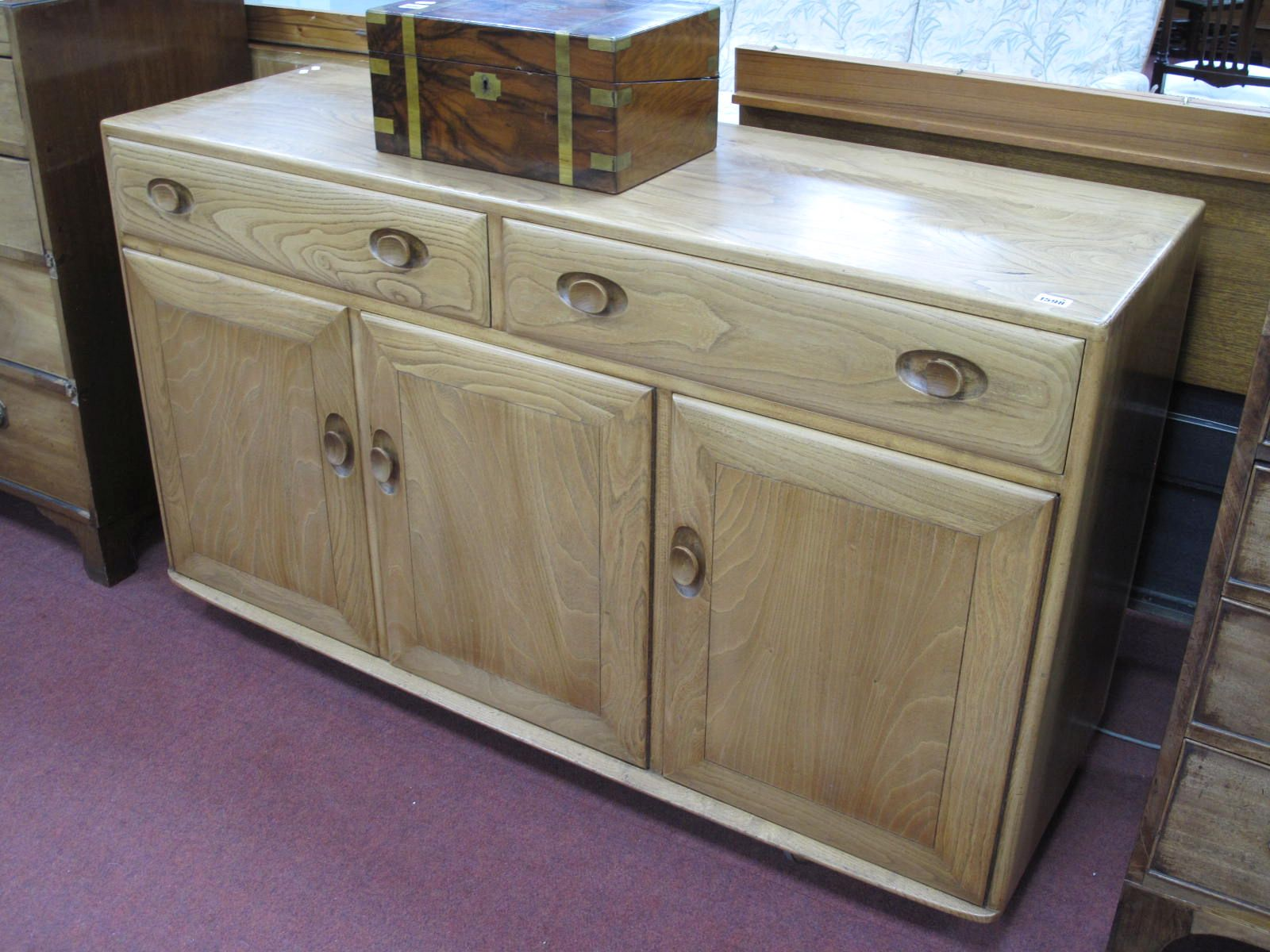 An Ercol Sideboard, with two long drawers over three cupboard doors, on castors, 126cm wide.