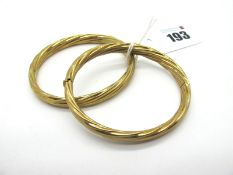 """A Pair of Modern Hinged Bangles, each of twisted design, hinged to snap clasp, stamped """"375"""" ("""