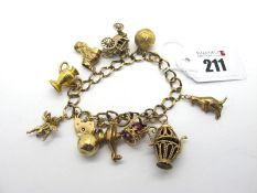 A 9ct Gold Charm Bracelet, to a 9ct gold heart shape padlock clasp, suspending assorted novelty