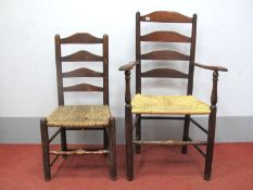 An Early XIX Century Ash and Elm Ladder Back Armchair, with shaped arms and rushed seat on turned