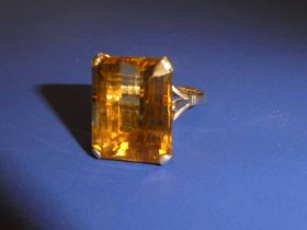 A 9ct gold Dress Ring set with a large rectangular Citrine, facetted edges, step cut, in a four claw