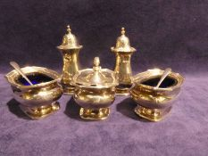 A mid century silver five-piece Cruet Set, consisting of a pair of pierced lid pepperettes, a pair