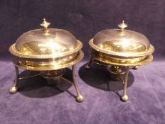 A pair of early 20th century silver plated Muffin Warmers, circular form on three footed balls